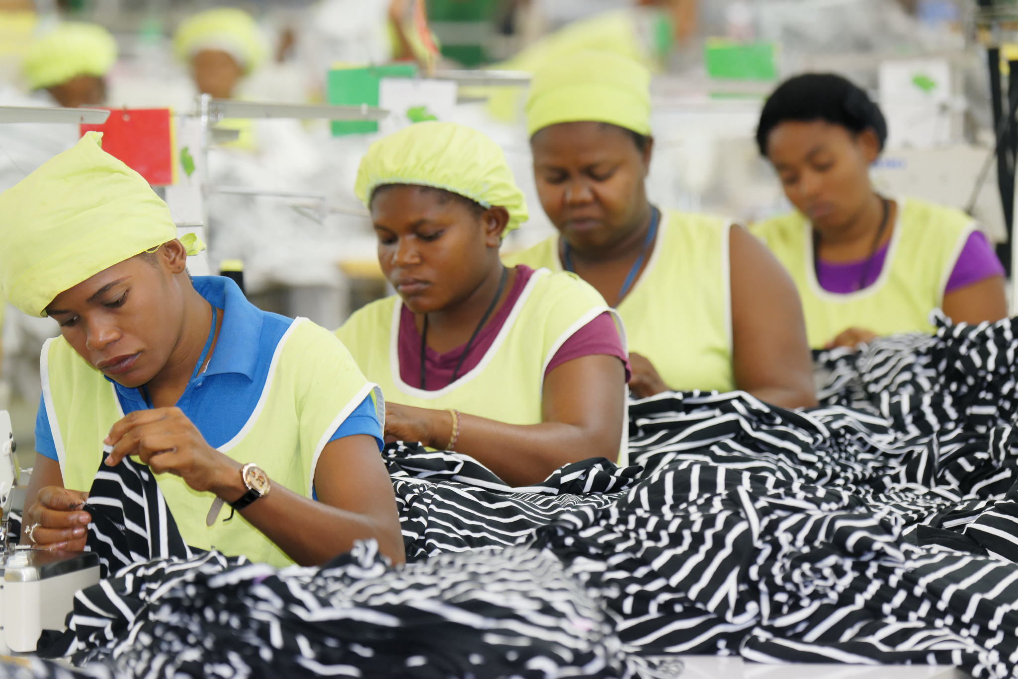 Haitian tailors are seen working on a production line in a local clothing plant. © BetterWork