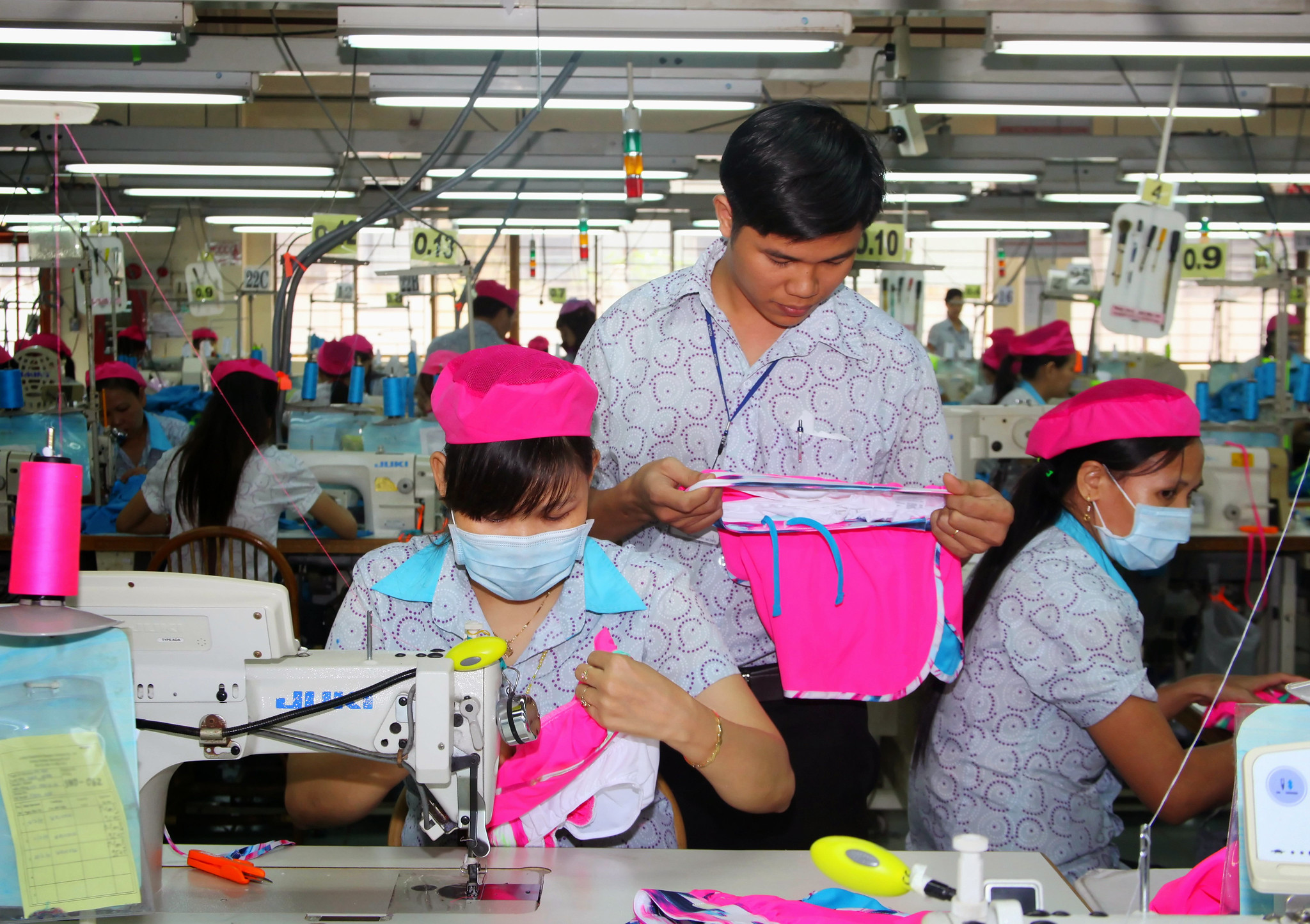 A supervisor oversees his employees' work in a clothing plant in Vietnam. © BetterWork