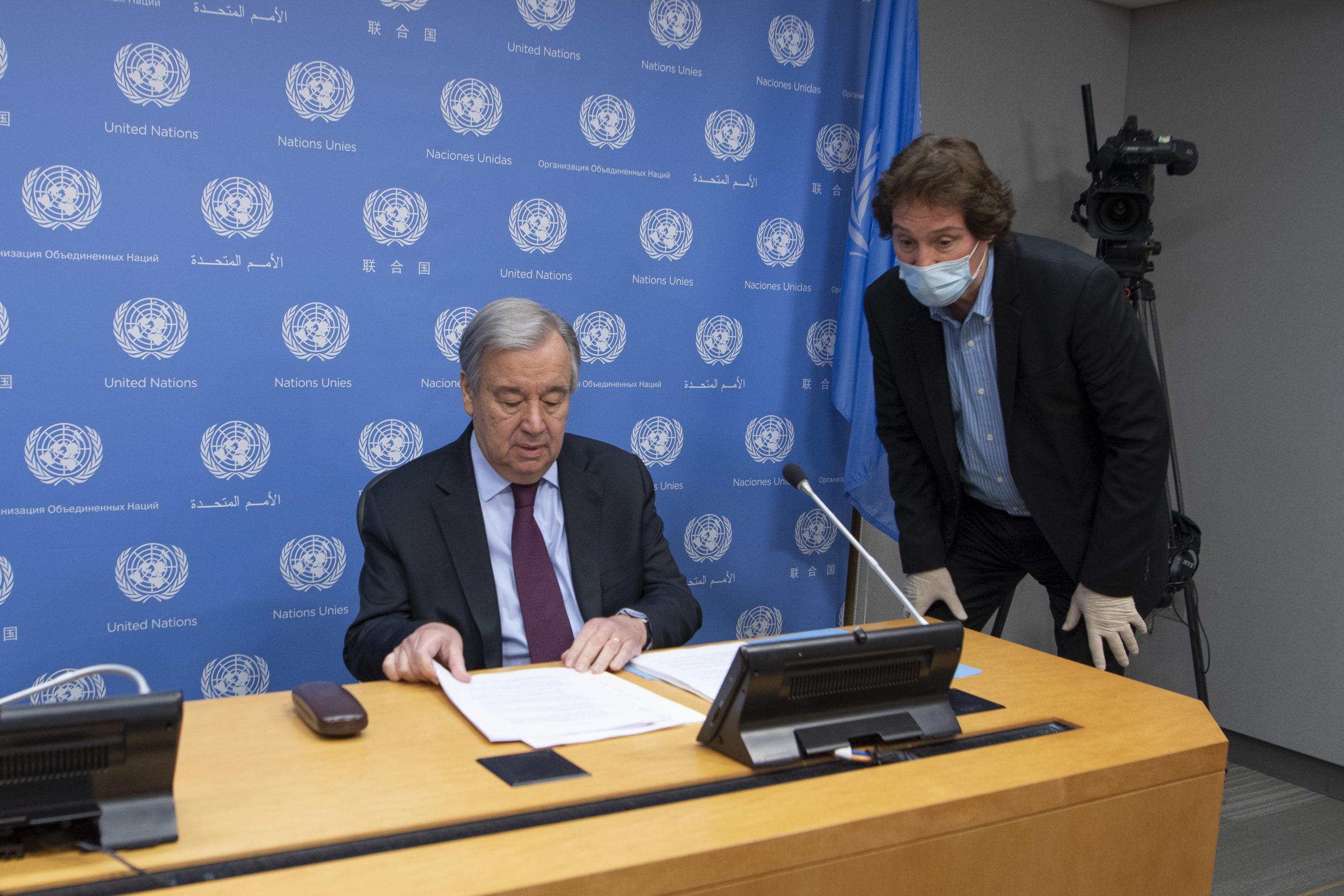 Secretary-General António Guterres (seated) speaks with a UNTV Studio Technician ahead of a virtual press conference. Credit: UN Photo/Eskinder Debebe