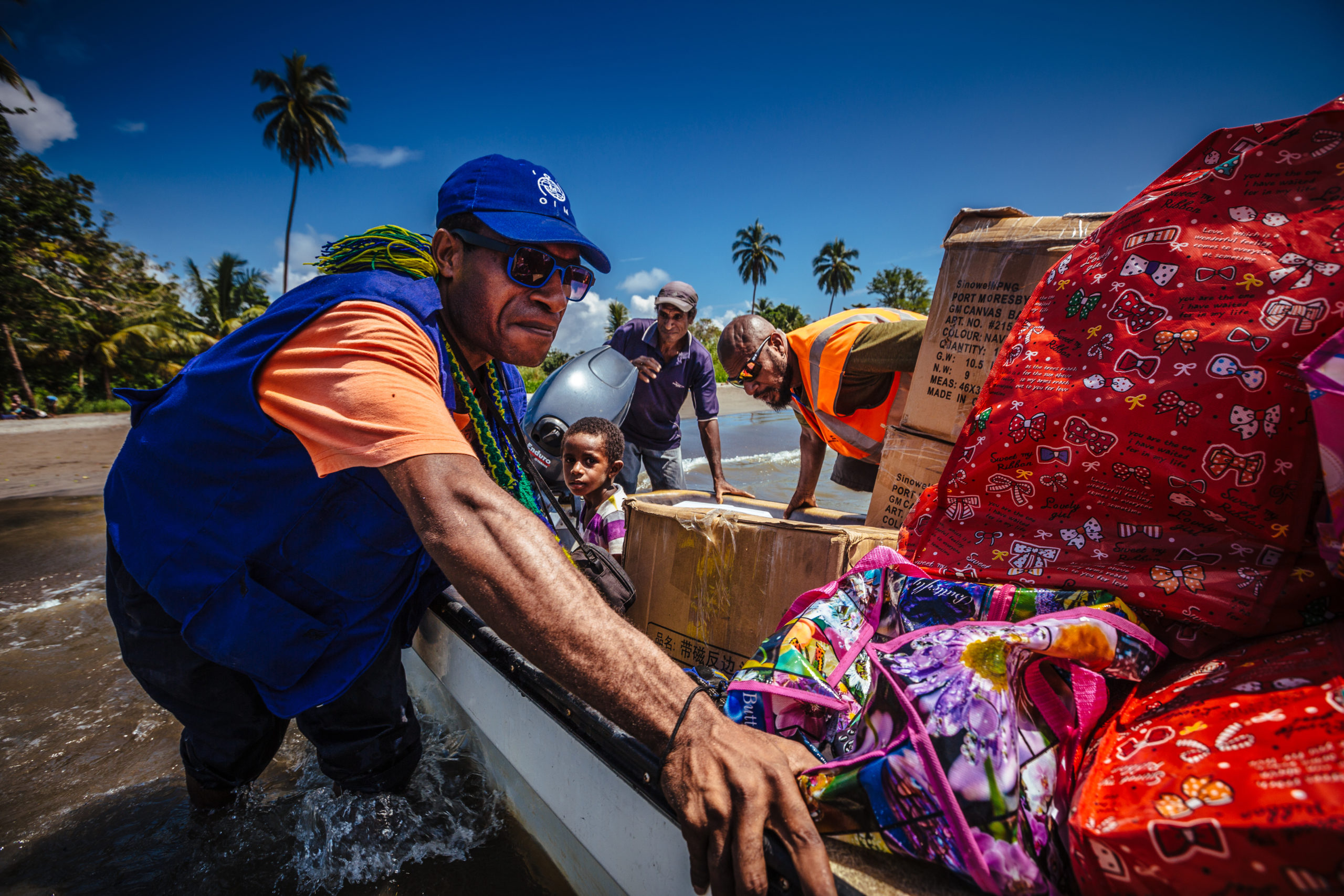 IOM staff pushing a boat full of emergency NFI's in order to reach flood affected villages located in jungle areas of Popondetta, Papua New Guinea. ©Muse Mohammed
