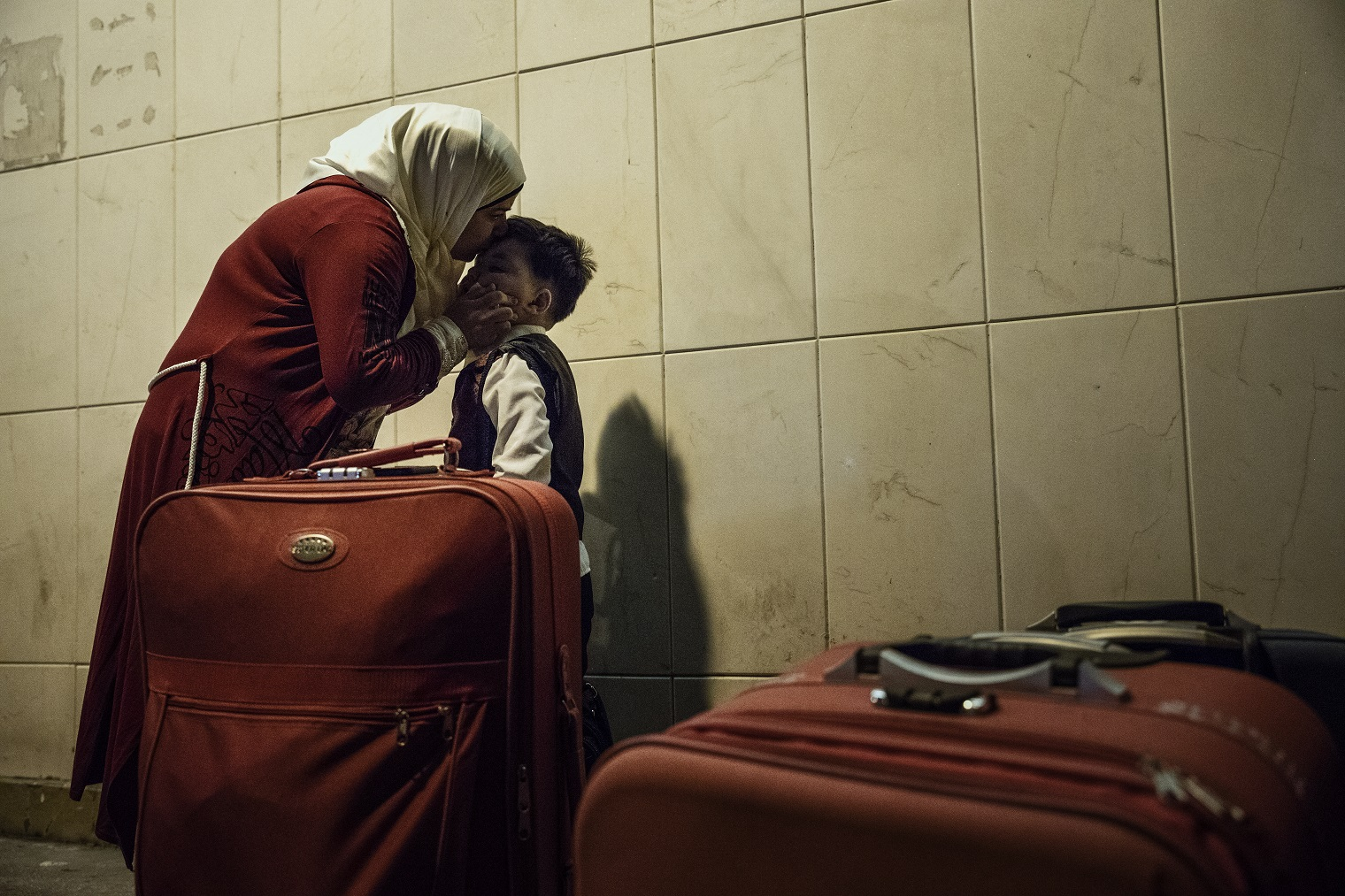 Syrian refugees in Lebanon. Aisha wipes away the tears from her son Zak as he says goodbye to his grandfather over the phone in Beirut, Lebanon. As the Syrian family waits for their taxi to the airport, today marks an end to a chapter in their lives where they have been living as refugees for several years. Recently, they found out that they are finally being resettled to Europe, where they will be able to start a new chapter of their lives. ©Muse Mohammed