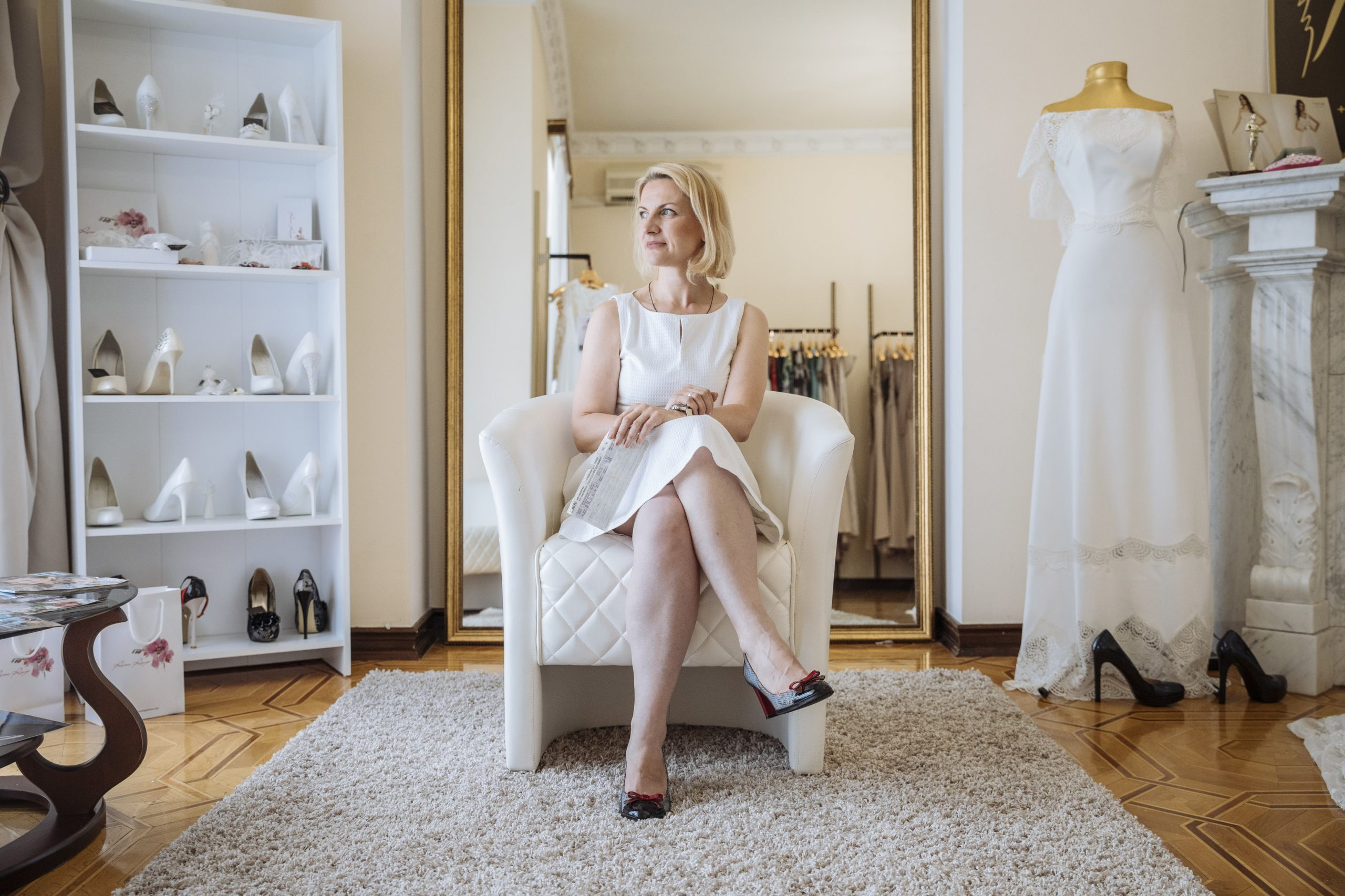 """Tatiana sits in her bridal shop in Kyiv, Ukraine. Originally from Donetsk, her local business was robbed in 2014 by armed groups and following the incident, decided to flee to the capital. She eventually befriended a wedding dress designer who was also displaced from the conflict. After seeing her friend fall on hard times, the two decided to open a business together designing and selling dresses. Over the next couple of years, Tatiana would go on to create her own business selling wedding dresses through the help of other women who were displaced from the conflict as well as an IOM business grant. """"There is something really special when you see a woman walk out of here with a dress saying, 'that's the one for me' and just knowing you played a part in that,"""" she said. To this day, Tatiana still carries the train ticket she bought to leave Donetsk as a reminder of how far she's come after fleeing her home from the conflict and to be appreciative of the good moments in life. ©Muse Mohammed"""