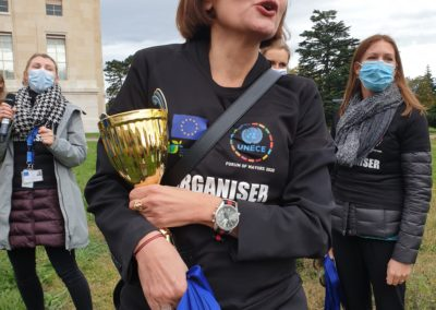 Paola Deda, organizer & Director at UNECE, cheering the team & holding tight onto the medals and cup.